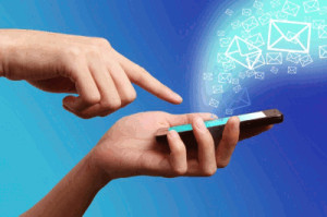 Pair of hands holding mobile phone with envelope icons floating out of phone