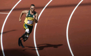 Athlete with two prosthetic legs running on race track